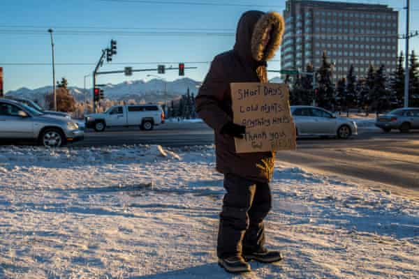 Carl, a 28-year-old who has been homeless for most of his life, holds a sign on a corner in Anchorage, when the temperature remained in the single digits.