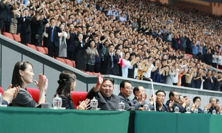 An image released by North Korea's official Korean Central News Agency shows Kim Jong-Un waving at the games and his sister, far left