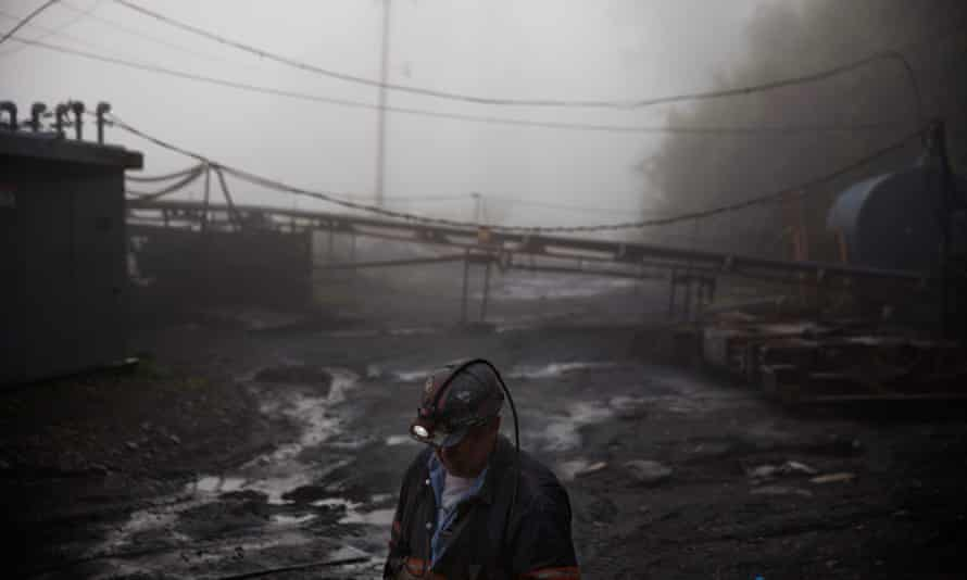 A coalminer walks through the morning fog before going underground in a mine less than 40in high in Welch, West Virginia.