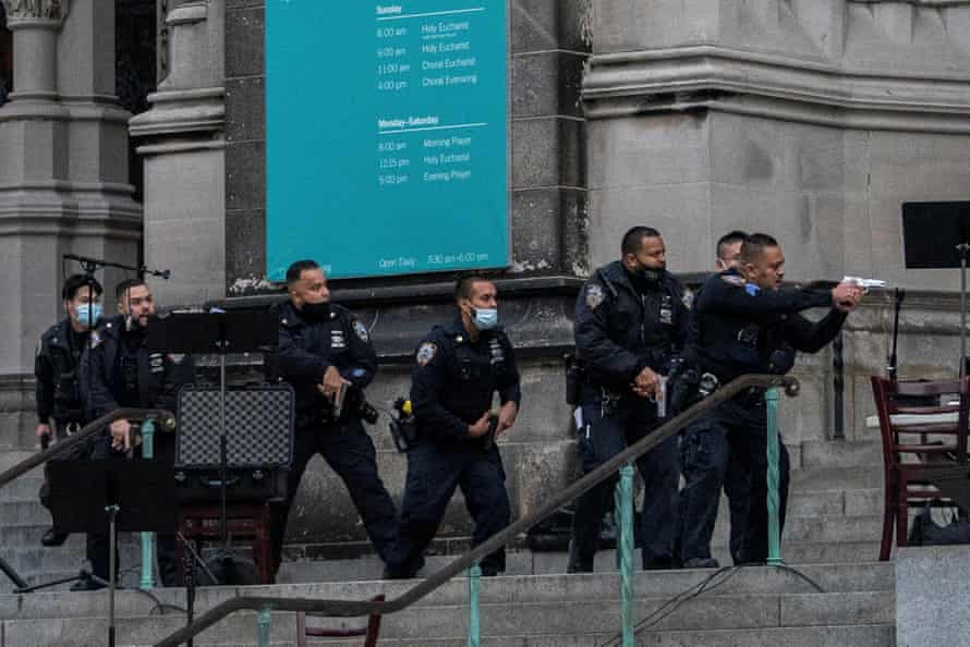 Police officers move towards the gunman on the steps of the Cathedral Church of St John the Divine in Manhattan.