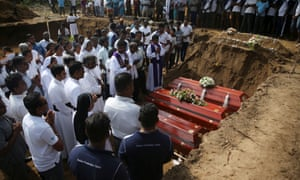 People attend a mass burial of victims at a cemetery near St Sebastian church in Negombo.