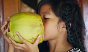 Better than butter? Maybe … a young girl drinking fresh coconut milk.