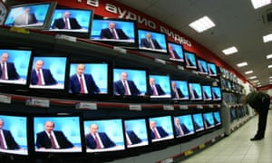 A man bends over in front of rows of TV sets showing the same image of Vladimir Putin