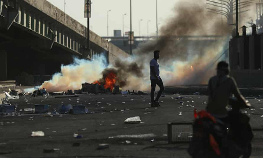 Iraqi security forces fire tear gas at protesters.