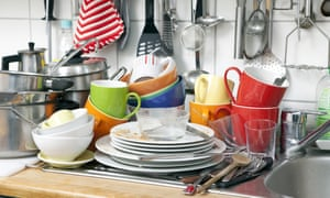 Pile of dishes next to kitchen sink