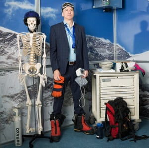 Hugh Montgomery in a suit, ski goggles and boots, with medical equipment in his hand, a skeleton and oxygen mask one side of him and a rucksack on the other
