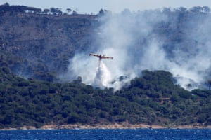A firefighting plane drops water to extinguish a fire on La Croix-Valmer from Cavalaire-sur-Mer, near Saint-Tropez