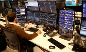 A financial trader works at his desk at CMC Markets in the City of London.
