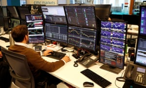 A financial trader works at his desk at CMC Markets in the City of London