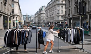 Retail workers move rails of clothes between stores on Oxford Street in London as non essential retailers prepare to re-open on Monday.