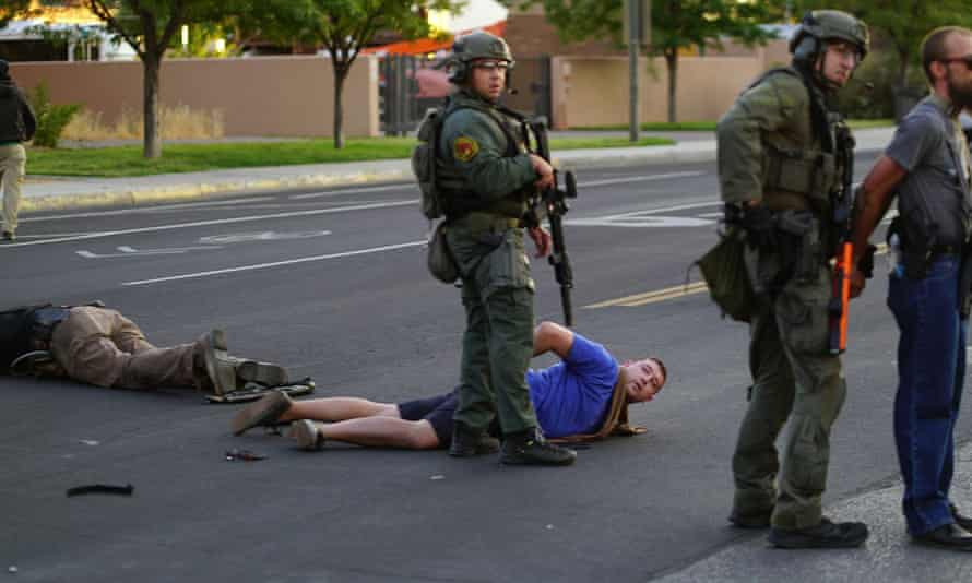 Steven Baca, center, taken into custody after he shot and wounded a man as the crowd tried to take down statue in Albuquerque, on 15 June.
