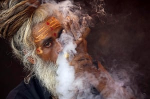<strong>Trimbakeshwar, India <br></strong>A naga sadhu, or naked Hindu holy man, smokes hashish inside his tent during Kumbh Mela, or pitcher festival. Hindus believe taking a dip in the waters of a holy river during the festival will cleanse them of their sins.