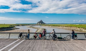 Cyclists take in a view of Mont Saint-Michel