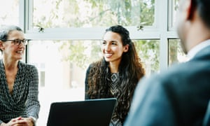 Smiling businesswoman leading team meeting in conference room