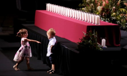 Charlotte O'Dwyer, daughter of firefighter Andrew O'Dwyer, reaches out to Harvey Keaton, son of RFS deputy captain Geoffrey Keaton, during the service