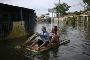 A man utilises a door as a makeshift raft as he transports a woman through the inundated streets of the Mata Redonda neighbourhood of Maracay.