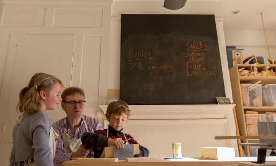 Teacher Geoff Davison with two six-year-old pupils,  Cecilia and Laith, in a woodwork lesson
