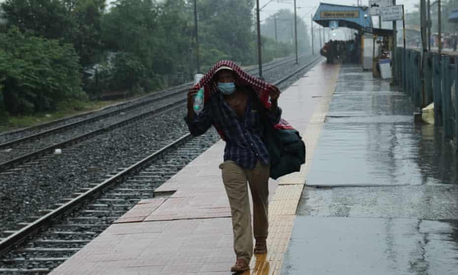 A man leaves a train station in heavy rain, in Kolkata, India