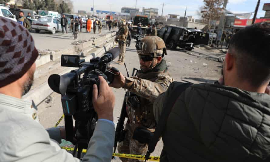 Afghan security police block a TV journalist from filming at the site of bombing attack in Kabul in February. The city fell to the Taliban on Sunday.