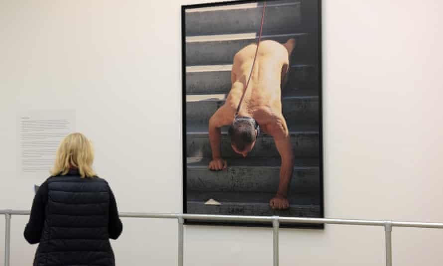 A viewer considers Oleg Kulik's work.
