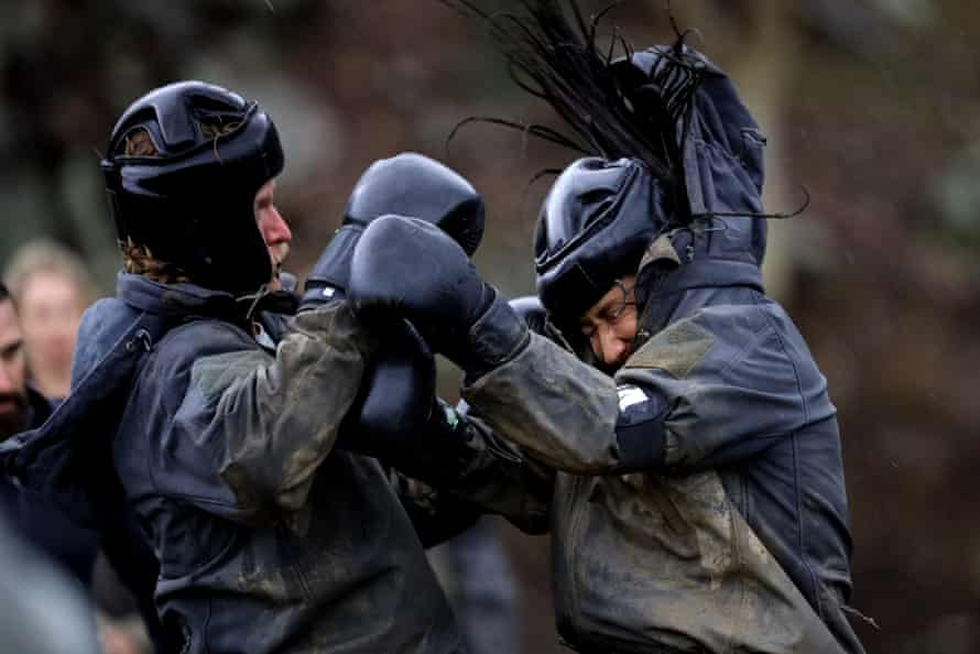 two people boxing in muddy black gear