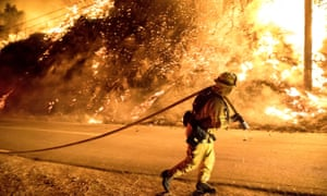A firefighter carries a hose closer to flames throwing embers in Filmore, California