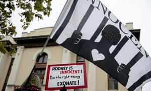 A woman holds a flag and sign during a protest against the execution of Rodney Reed on 13 November in Bastrop, Texas. Two days later the Texas criminal court of appeals granted a stay of execution.