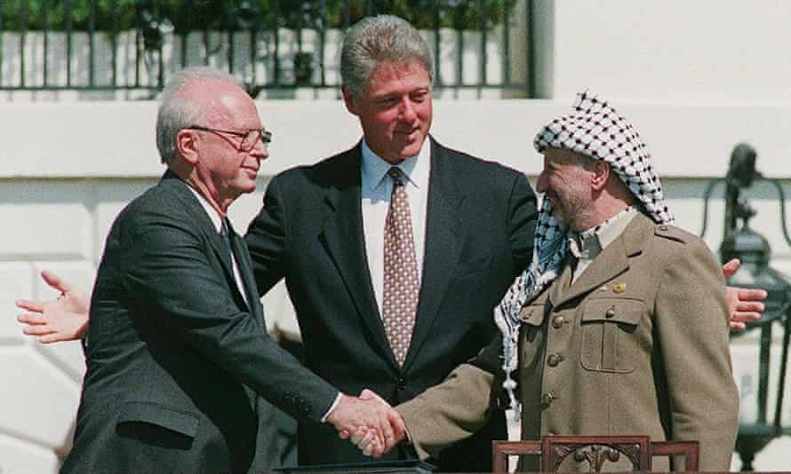 Clinton with Yasser Arafat (right) in his historic handshake with with Yitzhak Rabin on the White House lawn, September 1993.