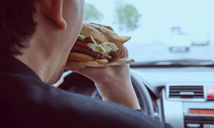 Man eating a burger while driving