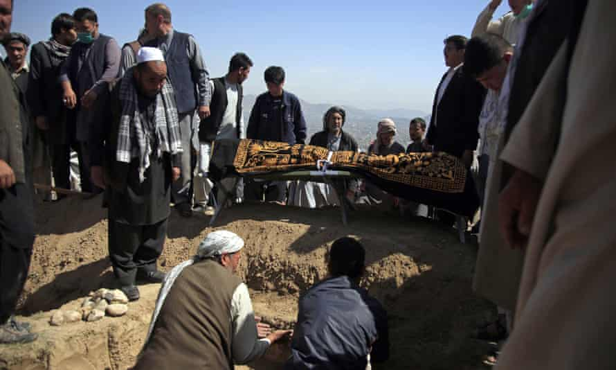 Afghan men bury a victim of the bombings at a cemetery west of Kabul