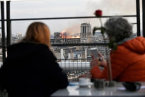 People look at the flames burning the roof of the Notre-Dame Cathedral in Paris