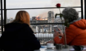 People look at the flames burning the roof of the Notre-Dame Cathedral in Paris.