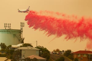 A water-bombing plane drops fire retardant on a bushfire in Harrington, 335km north east of Sydney on Friday