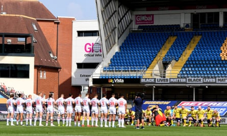 Wakefield Trinity's players link arms while the Wigan Warriors team take a knee in support of the Black Lives Matter movement at Headingley on Sunday.