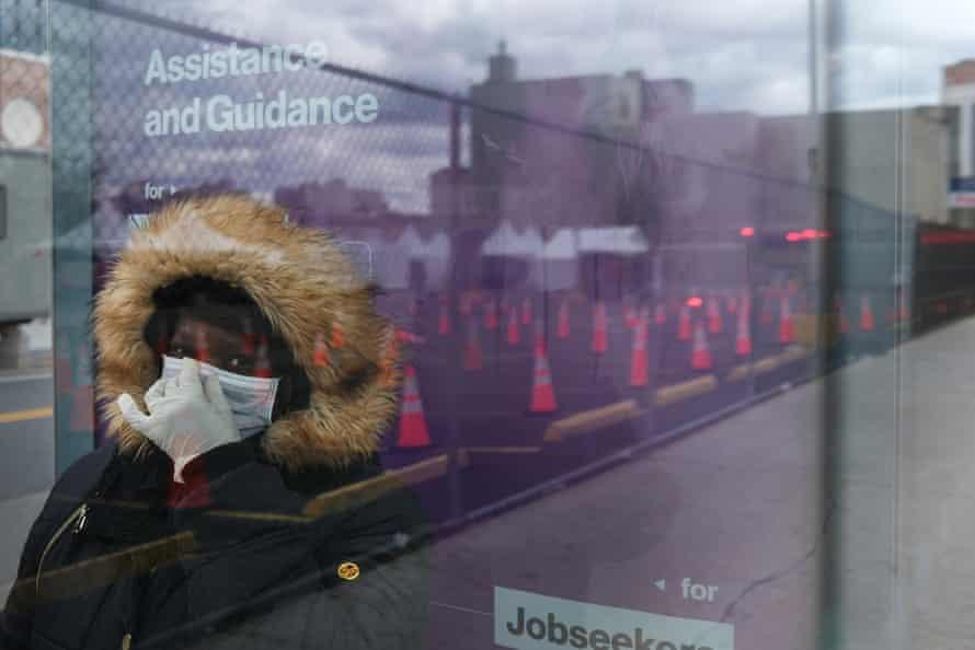 A woman waits for a bus near a coronavirus testing site in Brooklyn.