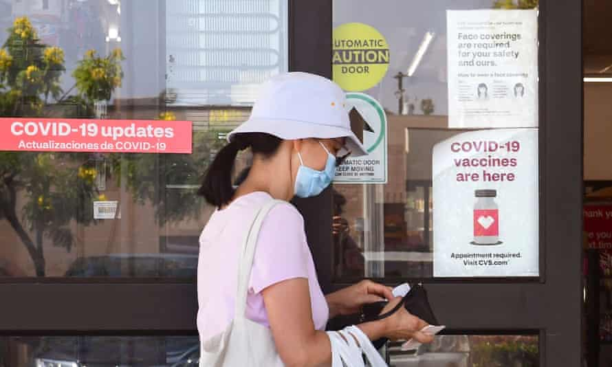A woman wearing a mask enters a drugstore in Monterey Park, California.