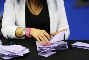 An official counting ballot papers at a counting centre in Glasgow this morning.