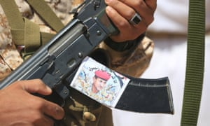 A Yemeni soldier holds a rifle with a photo of a top loyalist general killed in fighting with Iran-aligned Houthi rebels.