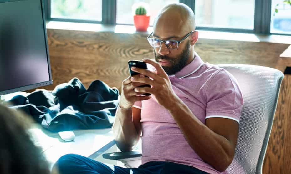Man with beard and glasses sitting at desk, checking smartphone