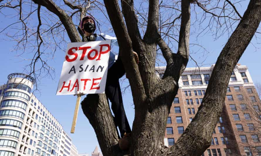 """An activist holds a sign on a tree during a """"DC Rally for Collective Safety - Protect Asian/AAPI Communities"""" at McPherson Square March 21, 2021 in Washington, DC."""