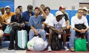 Residents wait inside the Corpus Christi natatorium in Texas to board a bus to San Antonio