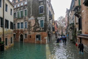 Venetians make their way through flooded streets