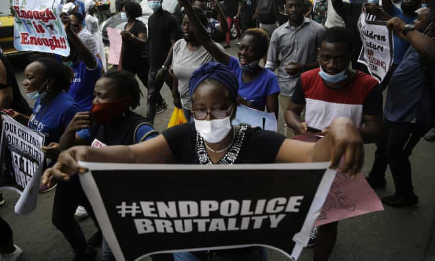 Woman in crowd holds 'end police brutality' sign
