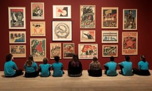 Schoolchildren in front of a wall of Soviet Union propaganda posters at the Red Star Over Russia exhibition.