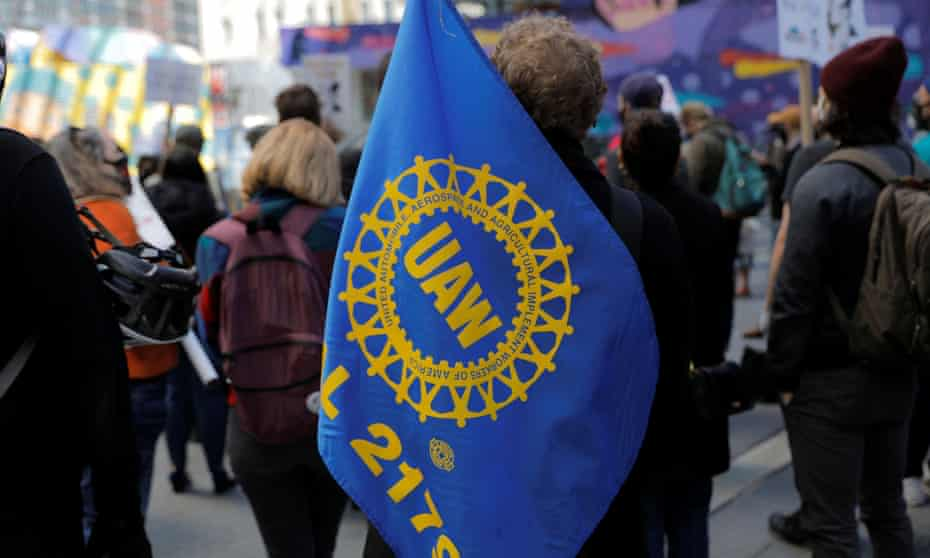 A person carries a UAW flag during a May Day rally in New York City.