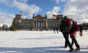 People stand in front of the Reichstag in the snow