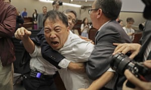 A pro-democracy lawmaker scuffles with security guards