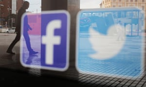 Facebook and Twitter logos are seen on a shop window