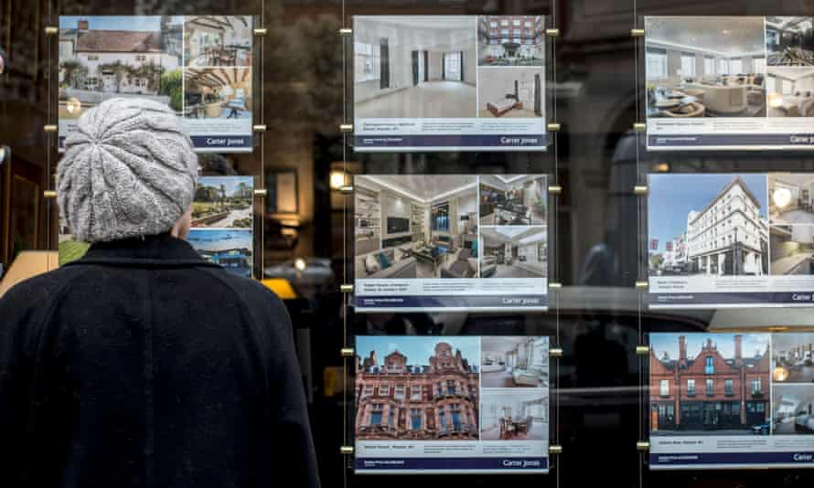 a woman looks at homes for sale in an estate agent window