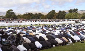 People pray during two minutes of silence for victims at Hagley Park in Christchurch on Friday.